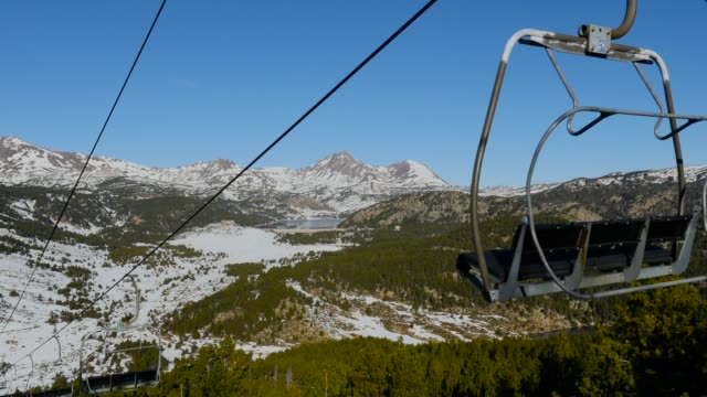 Chairlift with snowy mountains in the background.