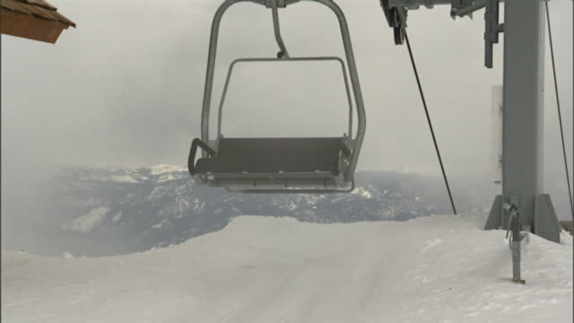 Chairlifts reaching top of lift empty chairs passing through frame Winter sports ski lift aerial lift skiing