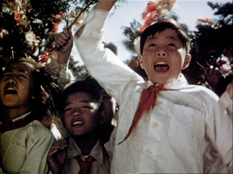 chairman mao gives speech to the people about much left to do / crowd cheers and waves flowers - mao zedong stock-videos und b-roll-filmmaterial