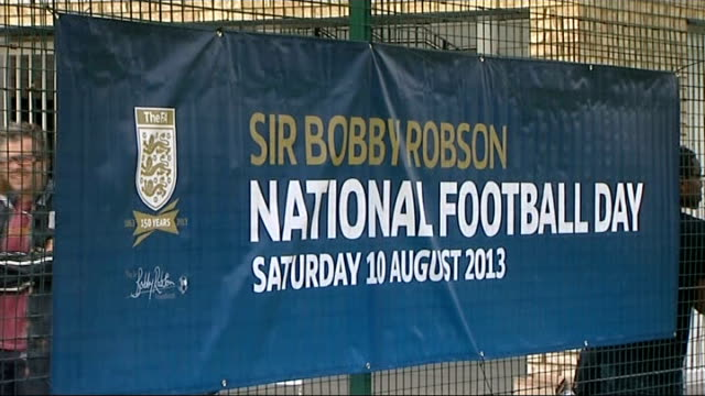 fa chairmans says qatar is too hot for the world cup 2022 greg dyke interview sir bobby robson national football day banner on fence - greg dyke stock videos & royalty-free footage
