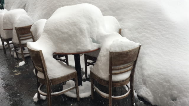 Chairs and tables covered with snow in the patio of a restaurant.