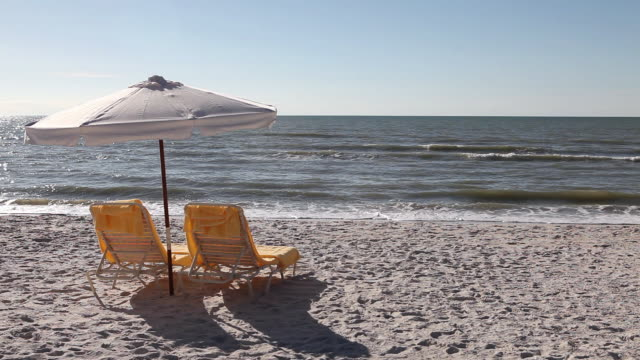 ws chairs and umbrella at empty beach and waves coming towards bank of sea / naples, florida, united states - naples florida stock videos & royalty-free footage