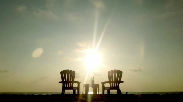 chairs in the beach with beers and lonely silhouette