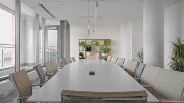 chairs surrounding conference table in office board room - sala conferenze video stock e b–roll