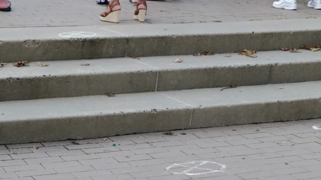 chalk outlines mark the ground to help maintain the social distancing guidelines at the carmine carro center for a 9/11 community vigil on september... - チョークの跡点の映像素材/bロール