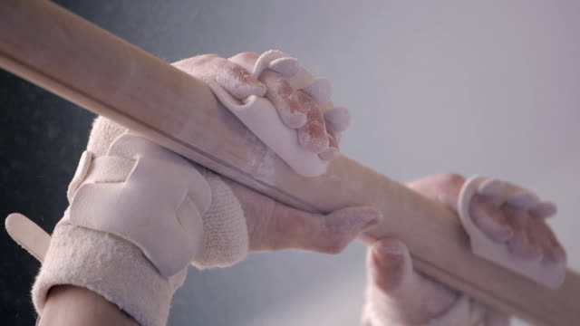 stockvideo's en b-roll-footage met  cu chalked and wrapped hands grabbing gymnastics horizontal bar / vancouver, british columbia, canada - gym