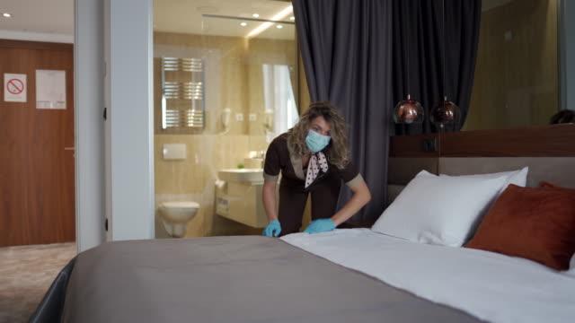 vídeos de stock, filmes e b-roll de camareira com máscara facial protetora fazendo cama em suíte de hotel - arrumado