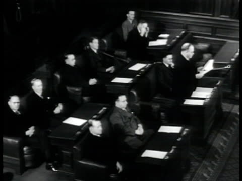 Chambers of House in session w/ members sitting one standing reading paper others sitting listening Different male member standing in Chamber reading...