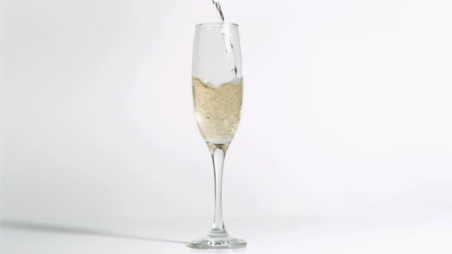 Champagne being poured in super slow motion in a flute