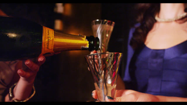 champagne being poured woman in background - champagne flute stock videos and b-roll footage