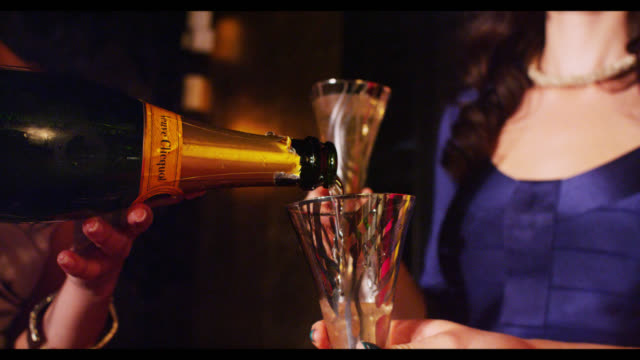 champagne being poured woman in background - champagne stock videos & royalty-free footage
