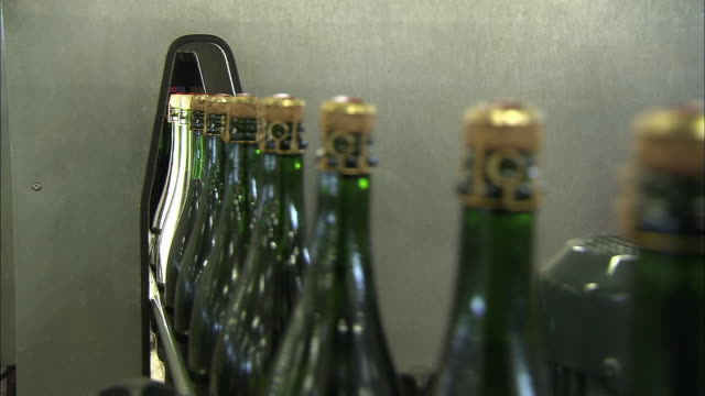 cu champagne bottles on moving conveyor belt enter small opening in machine throughout / reims, champagne, france - sektkorken stock-videos und b-roll-filmmaterial