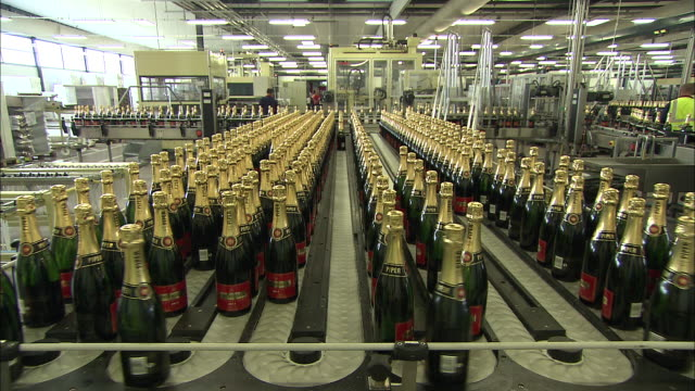 champagne bottles travel along conveyor belts in a bottling plant. - bottling plant stock videos & royalty-free footage