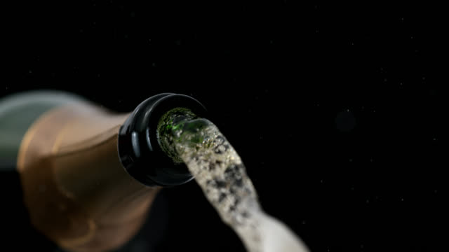 slo mo of champagne bubbles coming from the bottle - champagne stock videos and b-roll footage