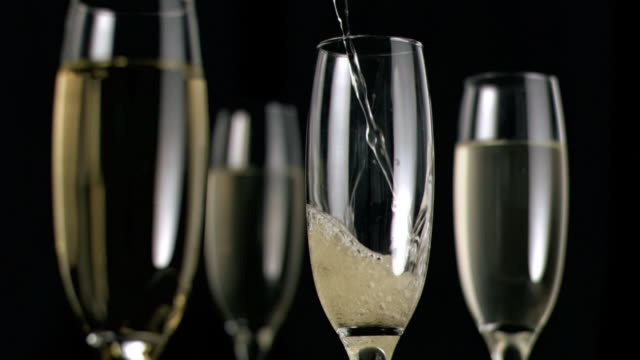 vídeos y material grabado en eventos de stock de champagne flowing in super slow motion in a glass - cuatro objetos