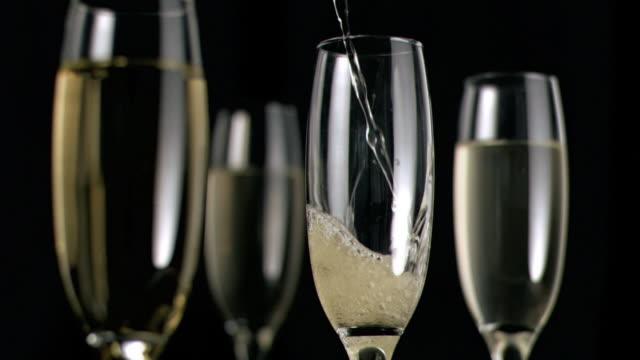 stockvideo's en b-roll-footage met champagne flowing in super slow motion in a glass - vier dingen