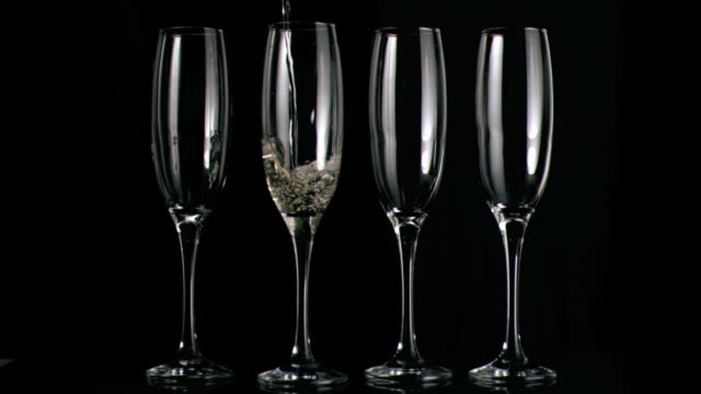 Champagne flowing in super slow motion in flutes