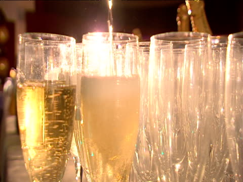 Champagne is poured into flute glasses