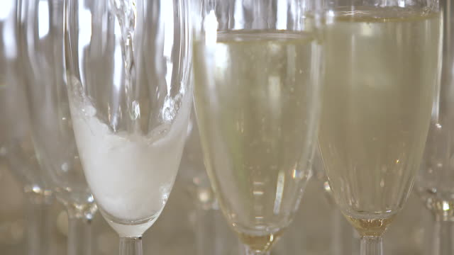 ECU Champagne pouring into glass with other glasses on table
