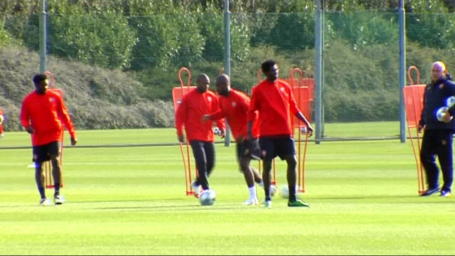 arsenal training ahead of fc porto match; wide shot of players running and kicking footballs back and forth in pairs - torschuss stock-videos und b-roll-filmmaterial