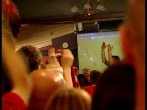 Liverpool win ENGLAND Liverpool Crowd of fans watching match then jumping up to cheer as celebrating first Liverpool goal SOT Fans waving arms as...
