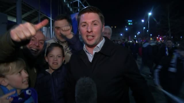 Leicester City through to quarter finals EXT / NIGHT Reporter to camera surrounded by cheering Leicester City fans/ Leicester fans cheering into...
