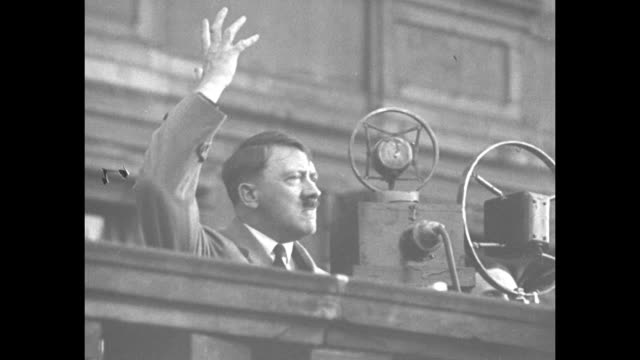 vídeos de stock, filmes e b-roll de chancellor adolf hitler speaking from balcony into microphones / huge crowd below listens - adolf hitler