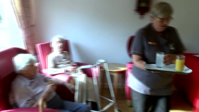 'chancellor's choice' effects of cuts on social care int elderly woman sitting in chair various of women chatting as sitting in care home care worker... - media interview stock videos and b-roll footage