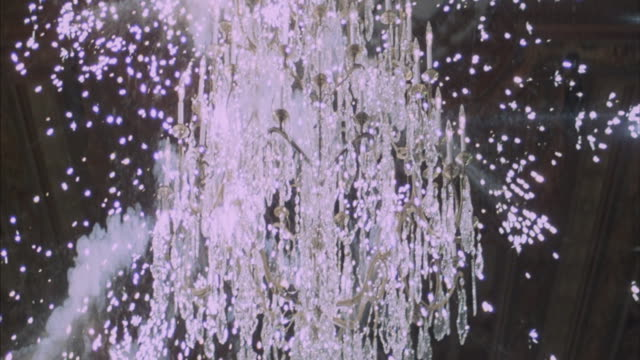 A chandelier explodes and falls from the ceiling.
