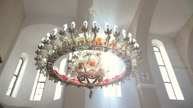 vídeos de stock, filmes e b-roll de candelabro que pendura no teto da igreja com sunbeams através do indicador - candelabro