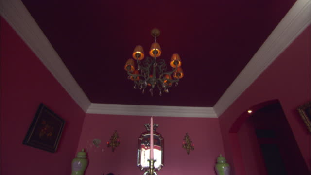 vidéos et rushes de a chandelier hangs from the purple ceiling of a pink dining room at la maison hotel in rio de janeiro. - palace