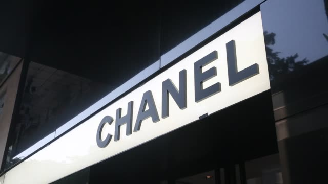 vídeos de stock e filmes b-roll de chanel logo displayed above entrance to store on canton road in the tsim sha tsui area of hong kong on tuesday oct 28 a shopper carries a shopping... - chanel