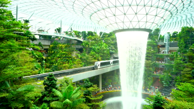 changi, singapore - circa september 2019 waterfall inside glass dome at jewel at changi with train passing across - falling water stock videos & royalty-free footage