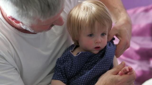 vídeos de stock e filmes b-roll de changing his daughter's clothes - pai dono de casa