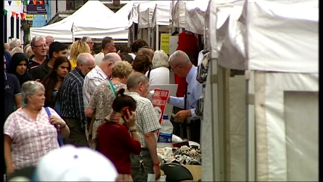 vídeos de stock, filmes e b-roll de channel 4 news pop up series lake district england cumbria keswick ext view over market stalls man and woman eating ice creams punch and judy show... - channel 4 news