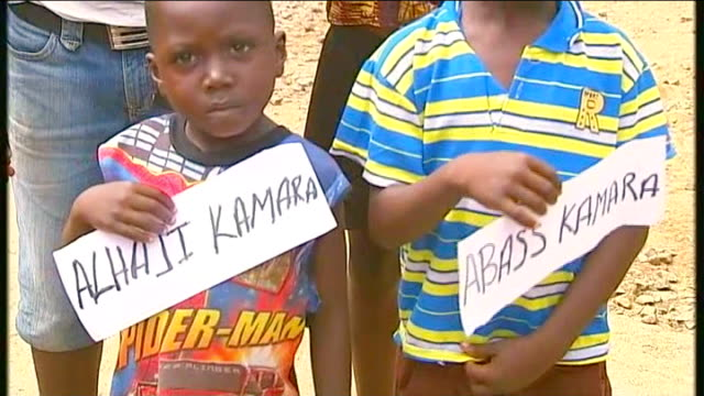 vídeos de stock, filmes e b-roll de channel 4 news review of the year november 2014 people in village including boy balancing container on head four kamar brothers [ebola orphans]... - channel 4 news