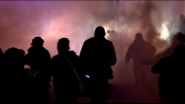 vídeos de stock, filmes e b-roll de channel 4 news review of the year november 2014 various shots riot police in riot gear on streets with tear gas smoke police cars with lights... - channel 4 news