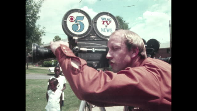 vidéos et rushes de channel 5 wlac cameraman working with 16mm film camera at outdoor event - 1972