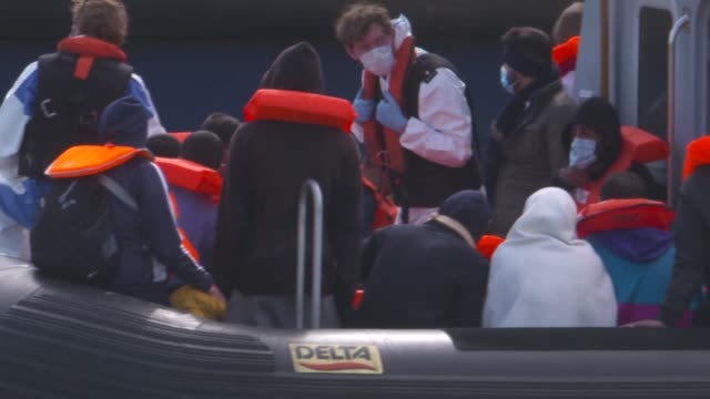 dover gvs; england: kent: dover: ext various of rescued migrants wearing life jackets on boat in harbour gvs fences around port perimeter various of... - rescue stock videos & royalty-free footage
