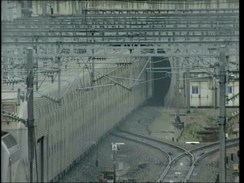 Channel Tunnel freight train along Freight train entering tunnel Sangatte Red Cross refugee centre INT Interior of warehouse housing refugees PAN...