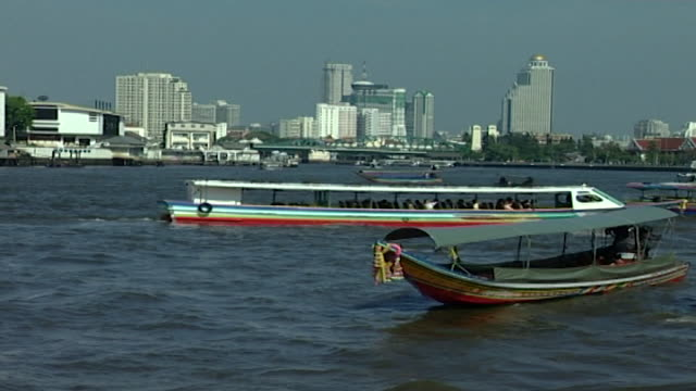 chao phraya river panleft with boats on the river the city's skyline can be seen in the distance - temple building stock videos & royalty-free footage