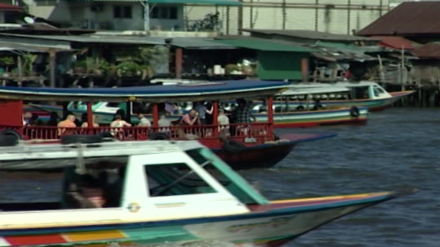 chao phraya river panright with a red ferry boat crossing the river - temple building stock videos & royalty-free footage