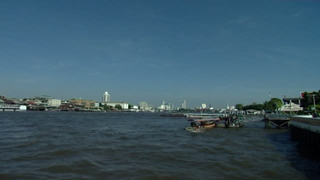 chao phraya river view of boats on the river near the dock of wat arun the city's skyline can be seen in the distance - temple building stock videos & royalty-free footage
