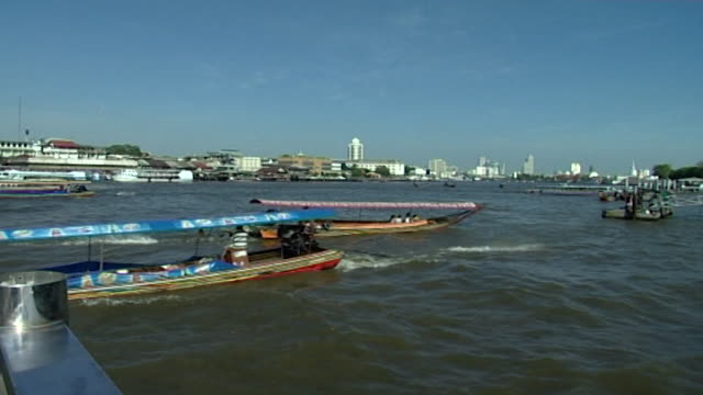 chao phraya river view of boats on the river the city's skyline can be seen in the distance - temple building stock videos & royalty-free footage