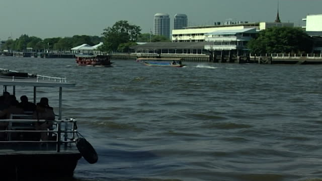 chao phraya river view of tourist boats chugging up and down the river seen from the dock of wat arun temple - temple building stock videos & royalty-free footage