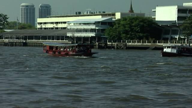 chao phraya river zoomin panright with a red ferry boat crossing the river - temple building stock videos & royalty-free footage