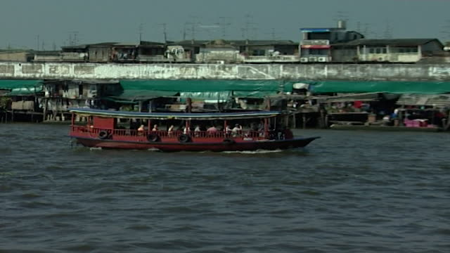 chao phraya river zoomout panright from a red ferry boat crossing the river - temple building stock videos & royalty-free footage
