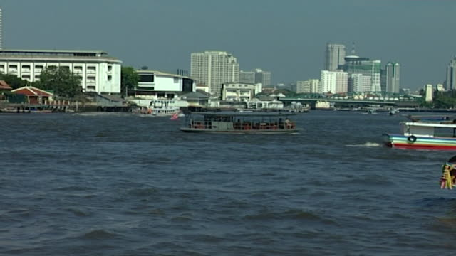 chao phraya river zoomout to reveal boats on the river the city's skyline can be seen in the distance - temple building stock videos & royalty-free footage