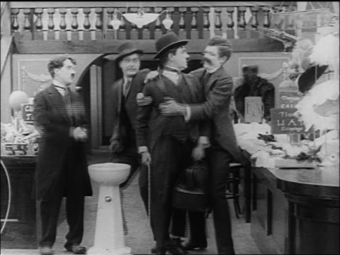 b/w 1916 chaplin look-alike (lloyd bacon) is grabbed by man (albert austin) + knocked on head - 1916 stock videos & royalty-free footage