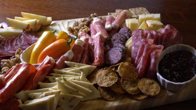 ディナーテーブルでシャルキュトリーボードを発表 - ブリーチーズ点の映像素材/bロール
